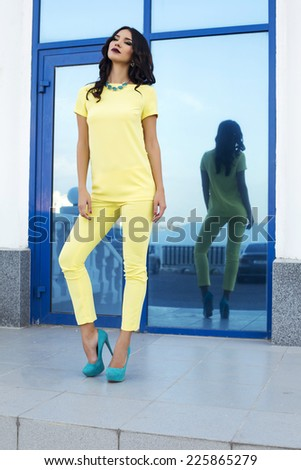 fashion outdoor photo of beautiful sexy woman with black hair in elegant yellow suit and blue shoes posing beside a big window - stock photo