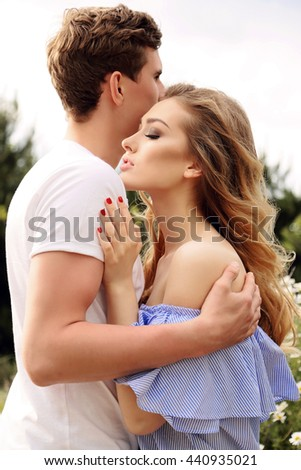 fashion outdoor photo of beautiful tender couple, posing in summer garden