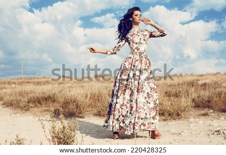 fashion outdoor photo of beautiful woman with dark curly hair in luxurious floral dress posing in summer field - stock photo