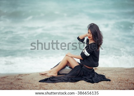 fashion outdoor photo of beautiful woman with dark hair  relaxing on summer beach