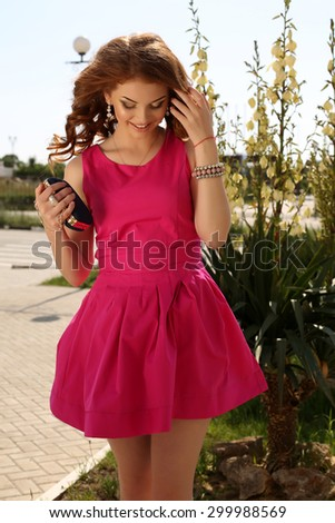 fashion outdoor photo of beautiful young woman with dark hair in elegant pink dress posing in summer park