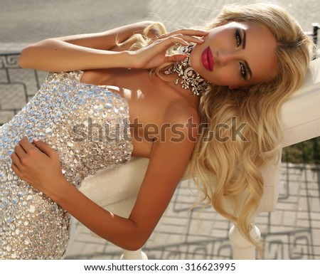 fashion outdoor photo of elegant beautiful woman with blond hair in luxurious sequins dress and silver accessories,posing in summer park  - stock photo
