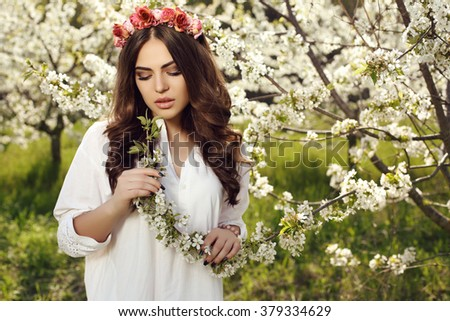 fashion outdoor photo of gorgeous sensual woman with dark hair in luxurious headband, wears elegant white dress, posing in blossom garden - stock photo