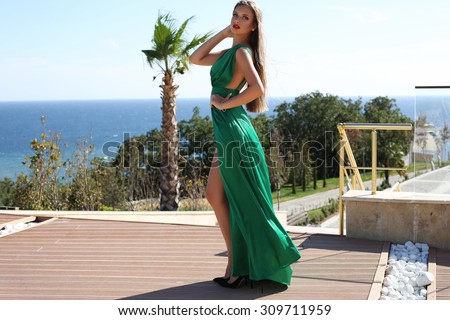 fashion outdoor photo of gorgeous sexy woman with blond hair in luxurious dress posing  beside swimming pool - stock photo