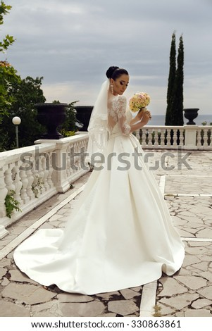 fashion outdoor photo of gorgeous young bride with dark hair in luxurious lace wedding dress,holding a wedding bouquet - stock photo