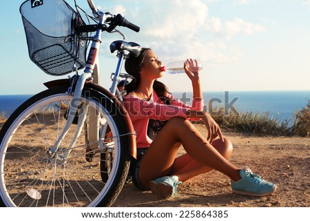 fashion outdoor photo of pretty young brunette wearing sportive clothes and drinking water sitting beside a bicycle on beach - stock photo