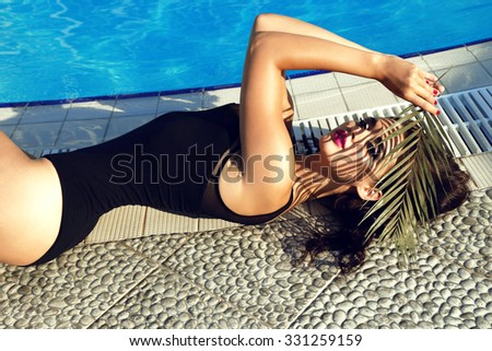 fashion outdoor photo of sensual beautiful woman with dark hair in elegant black swimsuit relaxing beside swimming pool,holding a leaf in hand - stock photo