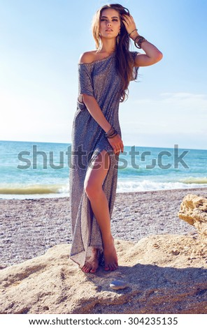Fashion outdoor photo of sexy beautiful elegant woman with long hair dressed in a luxurious evening dress posing on the summer beach next to the turquoise sea - stock photo