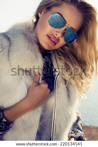 fashion outdoor photo of sexy beautiful woman with blond hair wearing fur jacket and aviator sunglasses