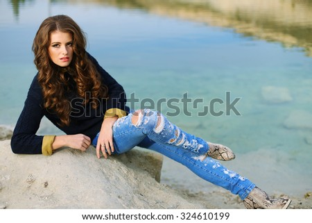 Fashion outdoor photo of sexy beautiful woman with dark curly hair and posing  against the backdrop of the lake and enjoying beautiful views - stock photo