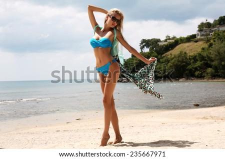 fashion outdoor photo of sexy beautiful woman with long blond hair wearing elegant bikini  and sunglasses,enjoying her vacation on island - stock photo