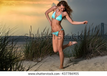 Fashion outdoor photo of sexy beautiful woman with slim fit body in blue bikini posing on the beach at sunset time. Horizontal shot. - stock photo