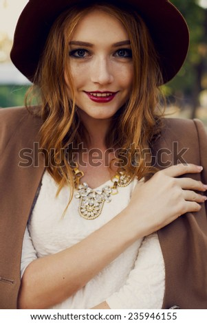 fashion outdoor portrait of cute young redhead woman in beige hat and jacket with beautiful necklace and curly hair in the citi park  - stock photo