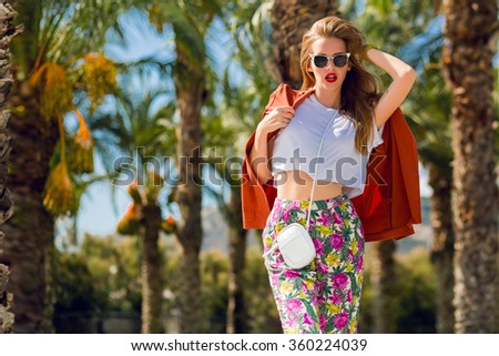 Fashion outdoor portrait  of fashionable blonde woman  posing   on palm trees  background .  Bright make up, orange jacket, sunglasses, bag in hands. Fashionable model walking in Barcelona. - stock photo