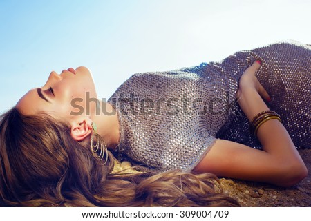 Fashion outdoor portrait of sexy beautiful elegant woman with long hair dressed in a luxurious evening dress posing on the summer beach  - stock photo