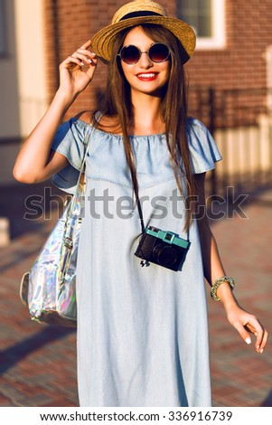 Fashion outdoor portrait of stunning brunette woman at stylish casual clothes, vintage hat and sunglasses, traveling alone at Europe with vintage camera and backpack , warm toned bright colors. - stock photo