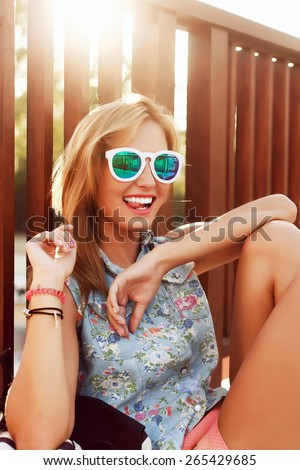 Fashion outdoor portrait of young beautiful sensual blonde woman in summer having fun sitting on the street in sunglasses in evening sunset  - stock photo