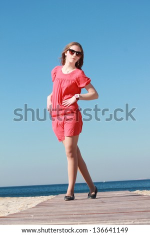 Fashion outdoor portrait of young girl in a summer style by the sea