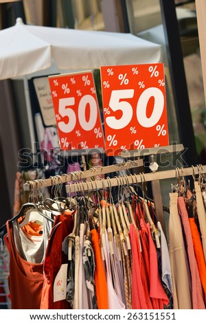 Fashion outlet. Sale in a clothing store - 50 percent discount sign at a clothes rack on the sidewalk outside the store - stock photo