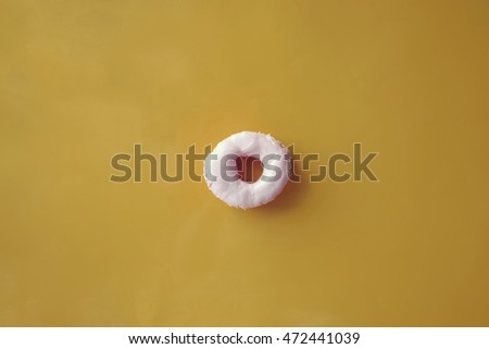 Fashion pastel pink donut on yellow background. Sweet donut. Donut background. Toned image.