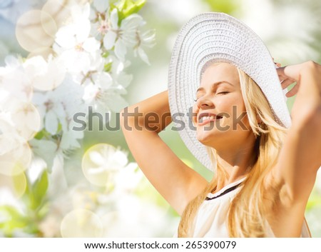 fashion, people and summer holidays concept - beautiful woman in hat and dress sunbathing over green blooming garden background - stock photo