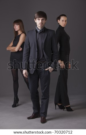 fashion people - one man and two women posing over grey background - stock photo