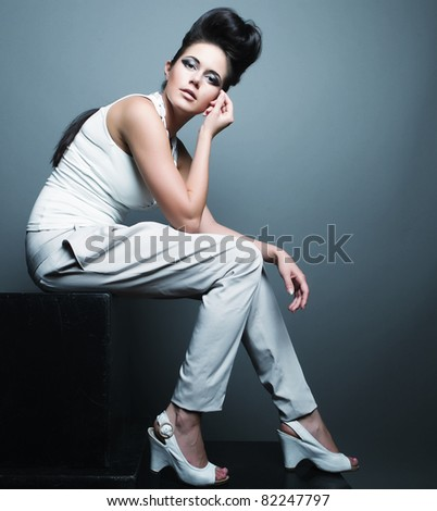 Fashion photo, a model is posing over grey background - stock photo