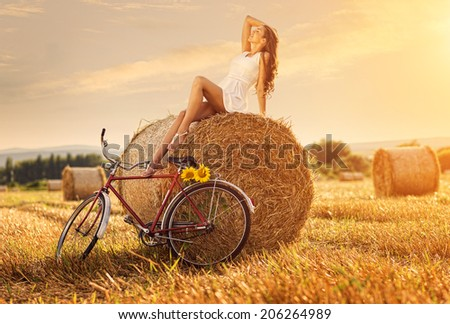 Fashion photo, beautiful woman sitting on a bale of wheat, next to the old bike  - stock photo