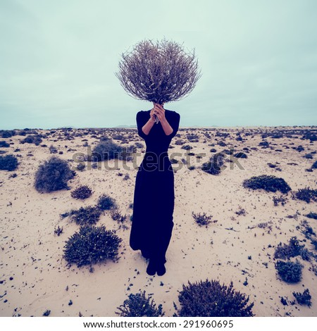 Fashion Photo. Girl in the desert with a bouquet dead branches - stock photo