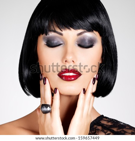Fashion photo of a beautiful brunette woman with shot hairstyle. Closeup girl's face with red lips and nails - stock photo