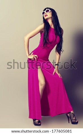 Fashion photo of a beautiful model in long summer dress and sunglasses. - stock photo