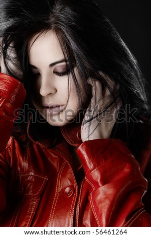 Fashion photo of a beautiful woman with purple smoky eyeshadow touching her black hair, in red leather jacket. - stock photo
