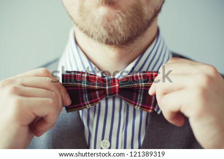 Fashion photo of a man with beard correcting his bowtie - stock photo