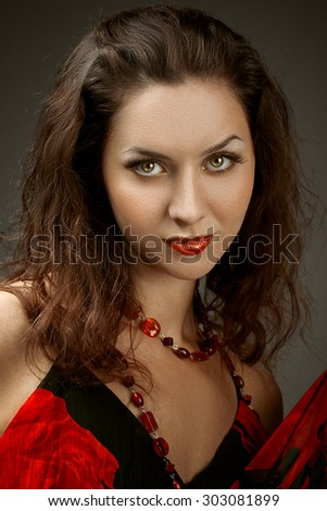 Fashion photo of a young woman with dark hair. Close-up portrait