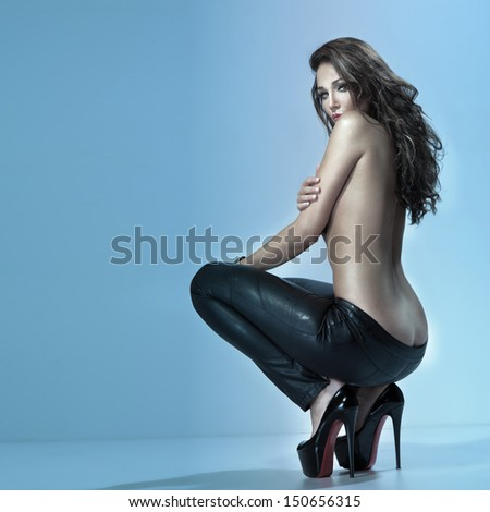 Fashion photo of attractive brunette woman in sensual pose. Long curly hair. - stock photo