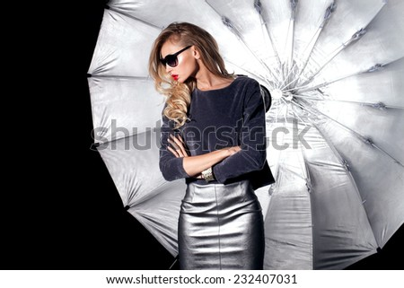 Fashion photo of beautiful blonde woman posing in studio. Girl with long curly hair. Elegant lady - stock photo