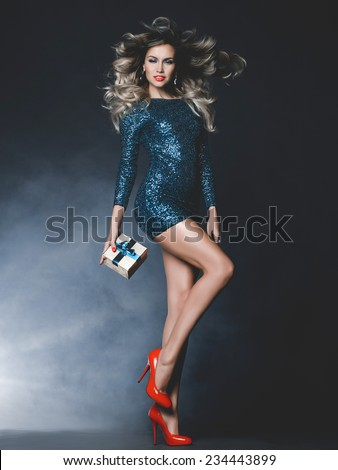 Fashion photo of beautiful dancing woman with a gift in her hands - stock photo