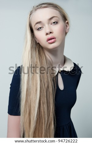 Fashion photo of beautiful female model in fancy dress and natural make up in studio - stock photo