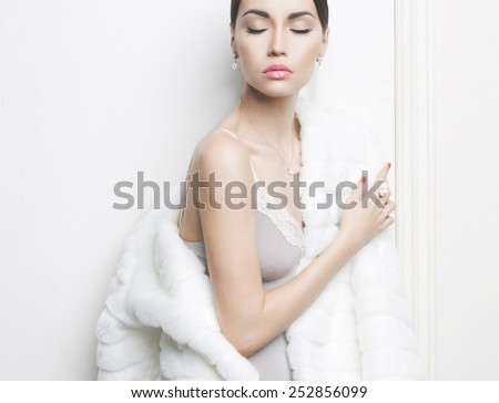 Fashion photo of beautiful lady in elegant white fur coat - stock photo