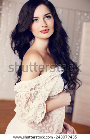 fashion photo of beautiful pregnant woman with long dark hair wearing lace dress