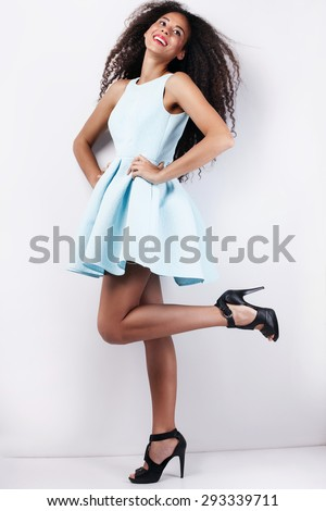 Fashion photo of beautiful smiling young girl in blue dress. Woman with long curly hair. - stock photo