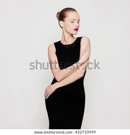 fashion photo of beautiful young woman in a black sexy dress.beauty brunette girl with red lips - stock photo