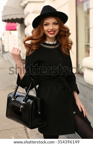 fashion photo of beautiful young woman with dark curly hair and charming smile,wears elegant clothes,walking by street