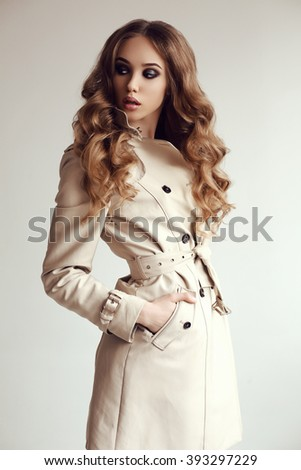fashion photo of beautiful young woman with dark curly hair wears elegant spring coat,posing in studio - stock photo