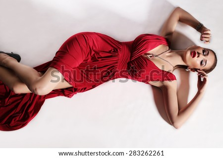 Fashion photo of elegance blond woman and slim sexy body wearing red dress with gold jewelry and heeled shoes lying at studio