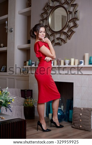 fashion photo of elegant and sexy woman in red dress posing at studio with classic interior near the mirror