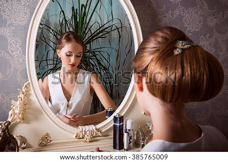 fashion photo of elegant and sexy woman in white clothes,  with beautiful hairstyle posing at bedroom with classic interior near the mirror - stock photo