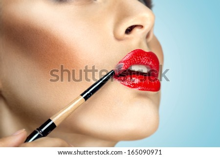 Fashion photo of face makeup demonstrating lips of a cute girl painted with bright lipstick with the hepl of brush.