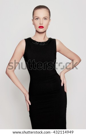 fashion photo of glamor beautiful young woman in a black dress.beauty brunette girl with red lips - stock photo