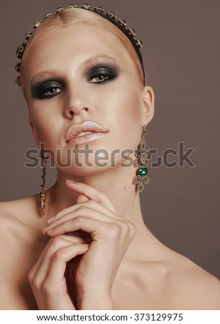 fashion photo of glamour beautiful woman with blond hair and smokey eyes makeup,with bijou and headband